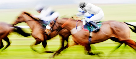 Blurred horses and jockeys racing from right to left