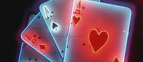 Neon sign with four playing cards, all aces